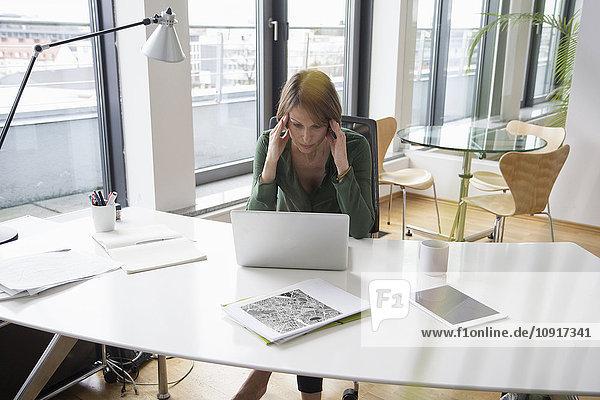 Konzentrierte Geschäftsfrau bei der Arbeit am Laptop am Schreibtisch