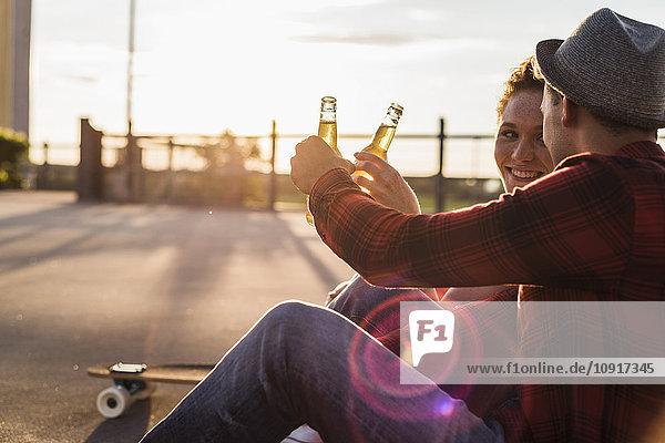 Junges Paar klirrende Bierflaschen bei Sonnenuntergang