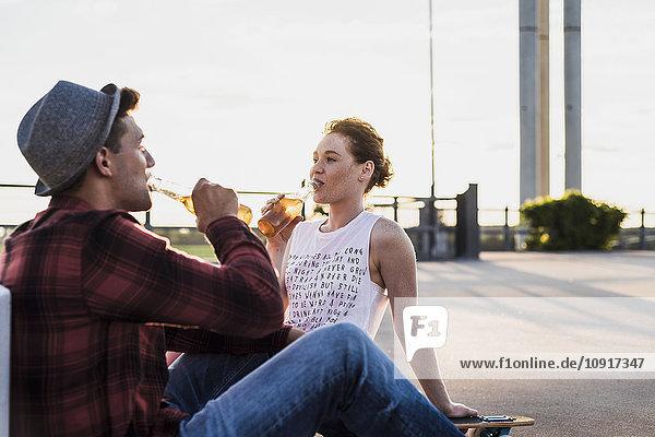 Junges Paar trinkt Bier aus Flaschen bei Sonnenuntergang