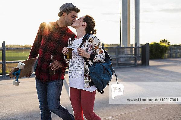 Junges Paar mit Bierflaschen und Skateboard-Küssen bei Sonnenuntergang