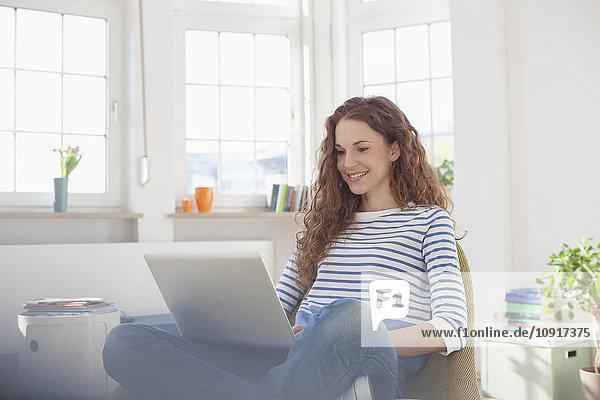 Frau zu Hause sitzend im Stuhl mit Laptop