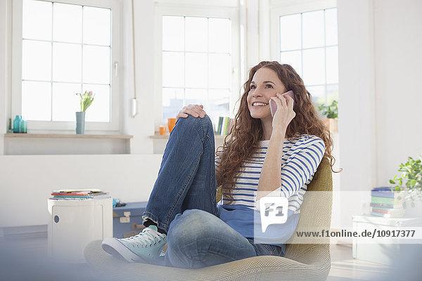 Frau zu Hause sitzend im Sessel und telefonierend auf dem Handy