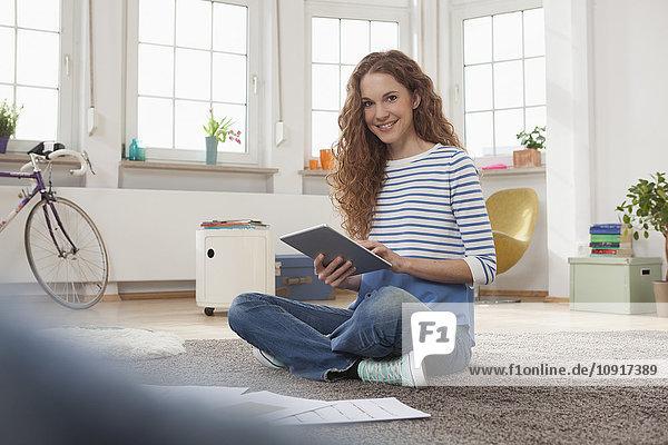 Frau zu Hause auf dem Boden sitzend mit digitalem Tablett