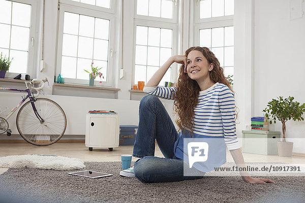 Lächelnde Frau zu Hause auf dem Boden sitzend