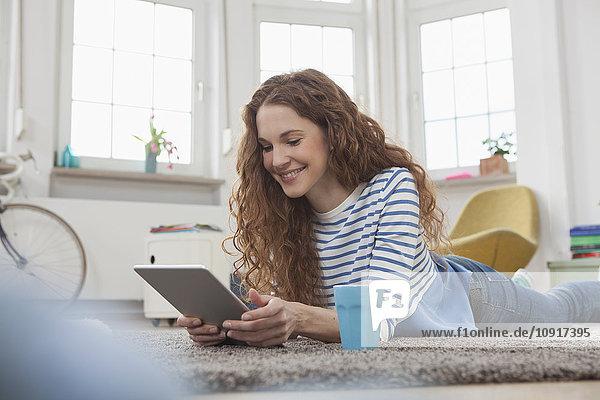 Frau zu Hause auf dem Boden liegend mit digitalem Tablett