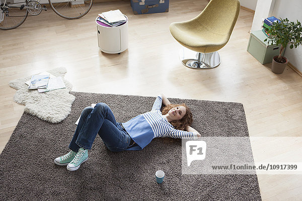 Relaxed woman at home lying on floor