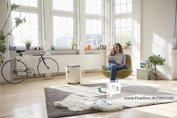 Frau zu Hause im Sessel sitzend mit digitalem Tablett