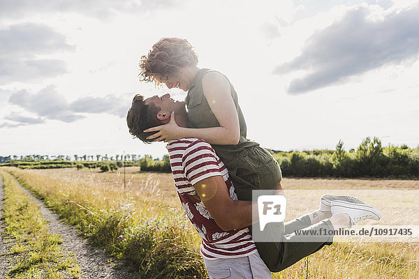 Glücklicher junger Mann hebt Freundin auf Feldweg hoch