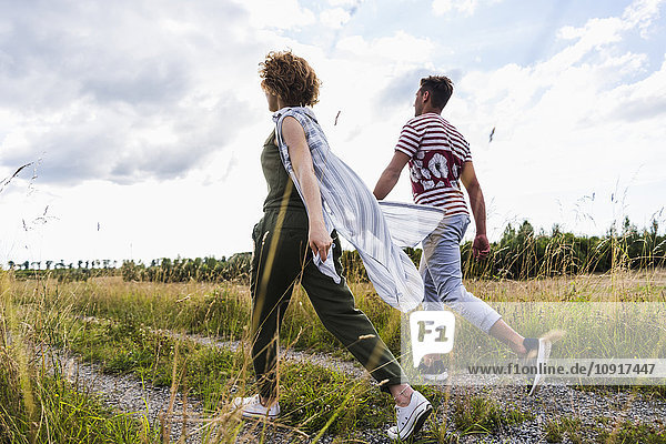 Young couple walking on field path