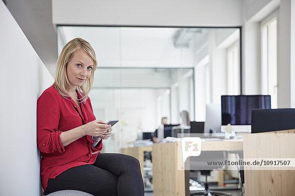Frau im Büro sitzend mit Smartphone