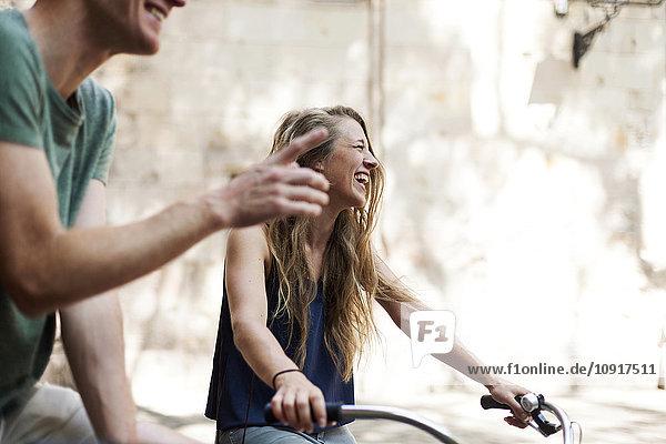 Lachende Frau mit Fahrrädern neben ihrem Partner