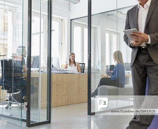 Geschäftsmann mit digitalem Tablett,  Mitarbeiter arbeiten im Hintergrund, Geschäftsmann mit digitalem Tablett,  Mitarbeiter arbeiten im Hintergrund