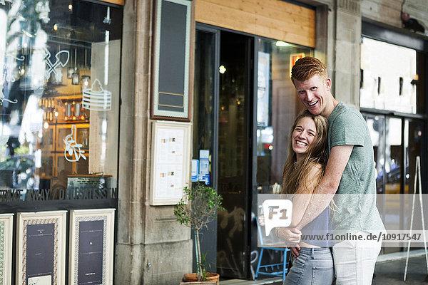 Glückliches Paar steht vor einem Coffee Shop