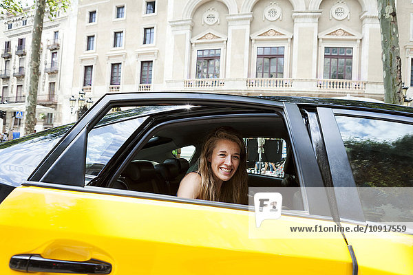 Spain  Barcelona  happy young woman looking out of taxi cab window