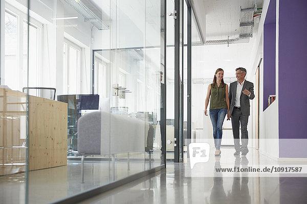 Geschäftsmann und Frau gehen den Büroflur entlang