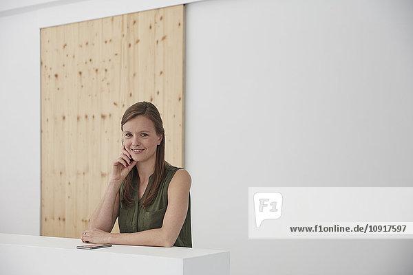 Junge Frau mit Smartphone  die sich im Büro auf das Hauptbuch stützt.