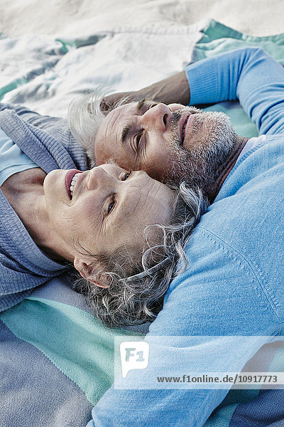 Ein glückliches Paar liegt Kopf an Kopf auf einer Decke am Strand.