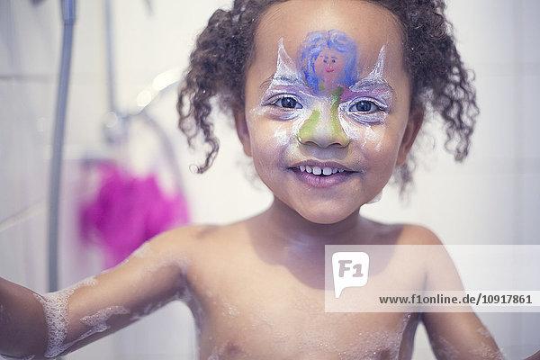 Porträt eines lächelnden Mädchens mit gemaltem Gesicht in der Badewanne