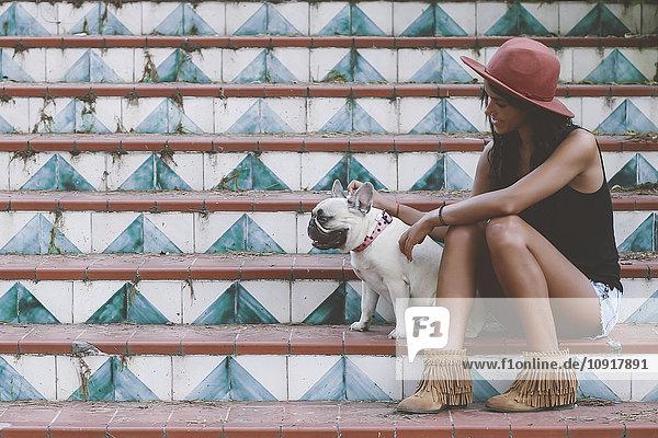 Frau sitzend mit ihrem Hund auf der Treppe Frau sitzend mit ihrem Hund auf der Treppe