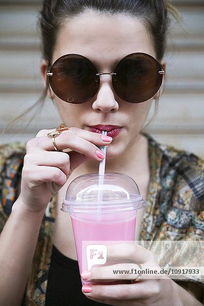 Porträt einer jungen Frau mit Sonnenbrille  die einen Smoothie trinkt.