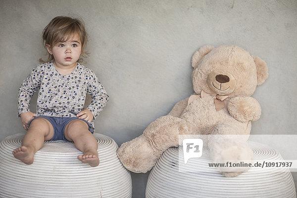 Seriöses Mädchen und Teddybär auf Hockern sitzend