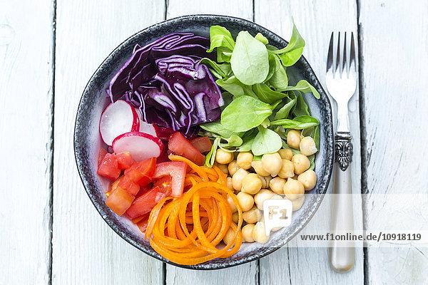Regenbogensalat in einer Schüssel mit Kichererbsen  Tomaten  Karotten  Rotkohl  Radieschen  Salat