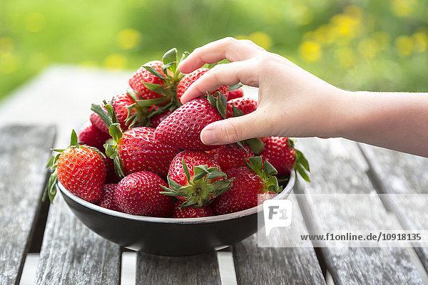 Mädchenhand nimmt Erdbeere