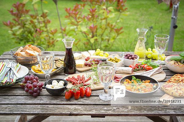 Vielfalt mediterraner Antipasti auf Gartentisch