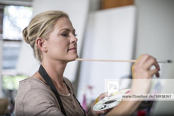 Frau im heimischen Atelier  malen  Palette in der Hand haltend