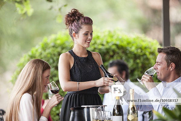Kellnerin mit Weinflasche im Restaurant