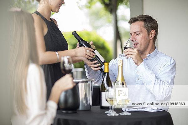 Mann im Restaurant bei der Verkostung von Rotwein