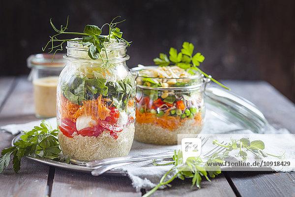 Regenbogensalate in Gläsern  Quinoa  Karotten  Erbsen  Rotkohl  Paprika  Mungbohnensprossen  der andere mit Tomaten  Mozzarella  Spinat  Erbsensprossen