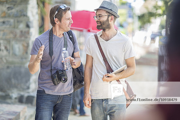 Two men walking and talking in the city