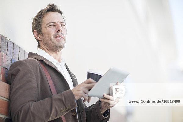 Mann mit digitalem Tablett und Kaffee für unterwegs