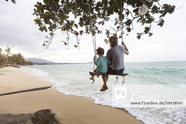 Thailand  Familie am Strand  sitzend auf Schaukel