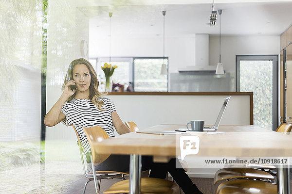 Frau am Handy am Tisch sitzend