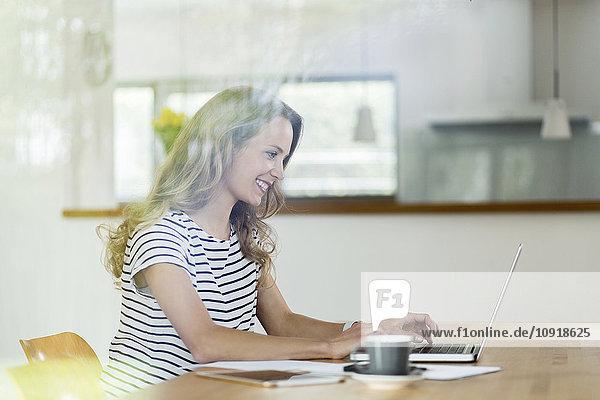 Lächelnde Frau mit Laptop am Tisch