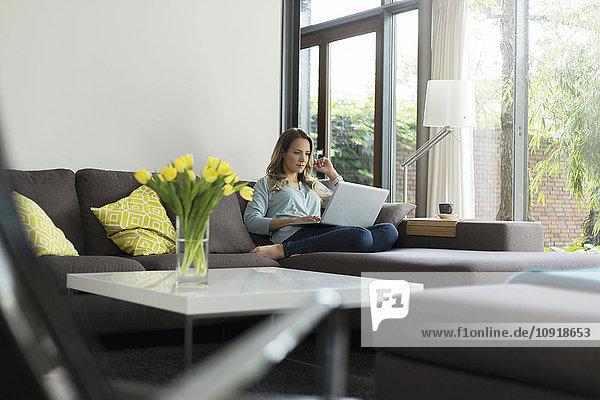 Frau zu Hause sitzend auf der Couch mit Laptop