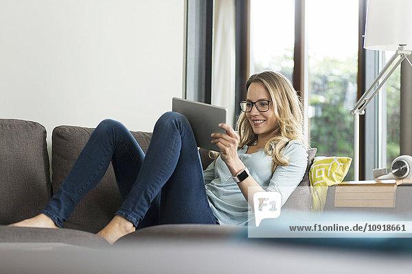 Lächelnde Frau zu Hause auf der Couch mit digitalem Tablett