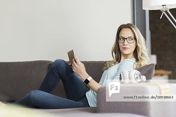 Frau zu Hause auf der Couch mit digitalem Tablett