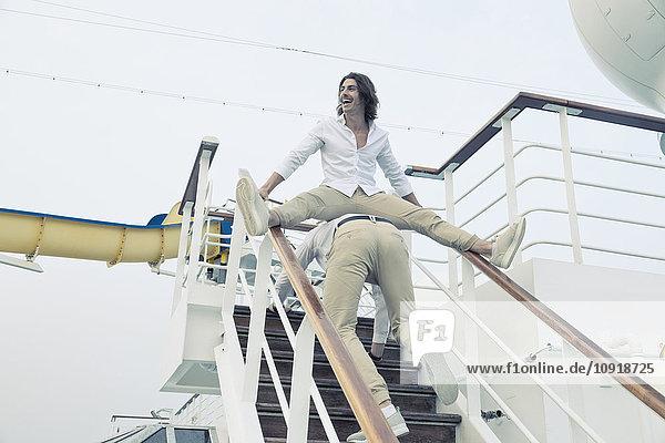 Zwei junge Männer  die sich auf einem Kreuzfahrtschiff herumtreiben.