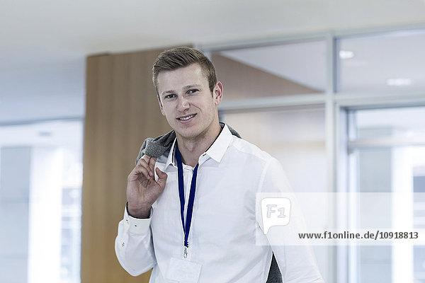 Porträt eines lächelnden jungen Mannes im Büro