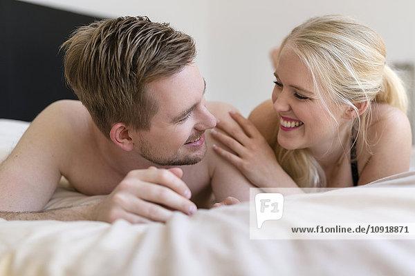 Glückliches Paar im Bett liegend