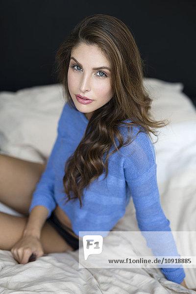 Frau mit Pullover auf dem Bett sitzend
