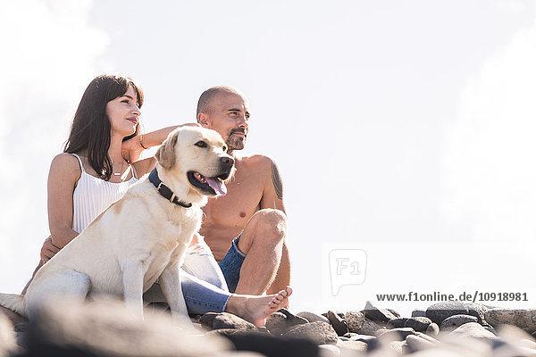Paar sitzend mit ihrem Hund am steinigen Strand