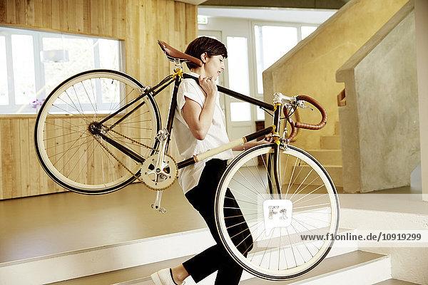 Frau mit Rennrad auf der Schulter im Büro