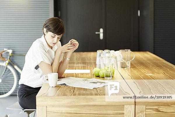 Frau liest Zeitung am Holztisch in einer modernen Kantine