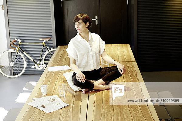 Entspannte Frau in Yogastellung auf Holztisch