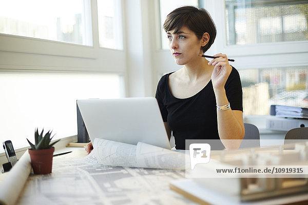 Architekt am Schreibtisch sitzend durchs Fenster schauend