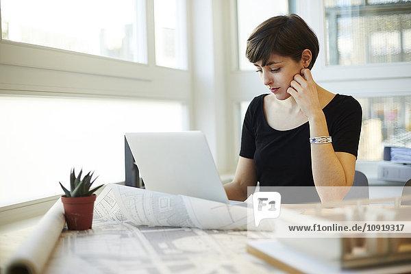 Portrait der Architektin mit Laptop in ihrem Büro
